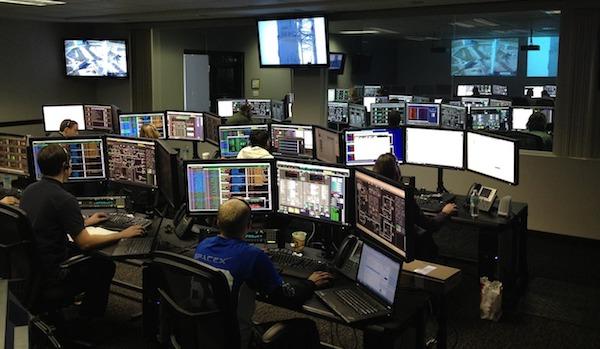 Sala com monitores e telas representando os painéis de indicadores necessários para um projeto